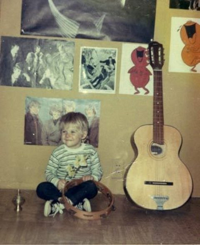 young kurt cobain picture alongside an acoustic guitar