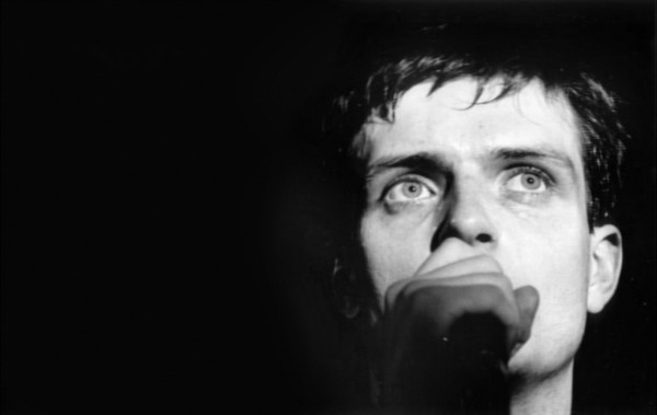 ian curtis on stage blue eyes close plan